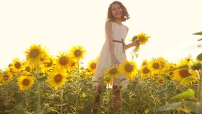 Happy little girl teen smelling a sunflower sneezes allergic to flowers on the field in summer. slow motion video. girl. Happy little girl teen smelling stock footage
