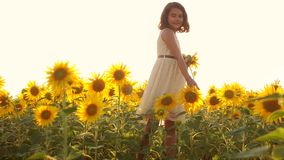 Happy little girl teen smelling a sunflower sneezes allergic to flowers on the field in summer. slow motion video. girl. Happy little girl teen smelling stock video footage
