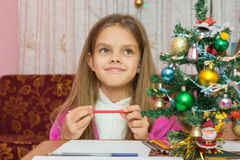 Happy little girl thinking of a gift for new year Stock Images