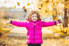 Happy little girl throws the autumn leaves in the air. Instagram filter Stock Images