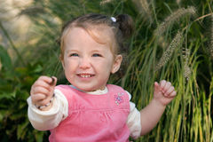 Happy little girl toddler excitedly showing off a pebble. Royalty Free Stock Photography
