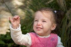 Happy little girl toddler excitedly showing off a pebble. Happy little girl toddler excitedly showing off a pebble while delicately holding out pinky finger royalty free stock images
