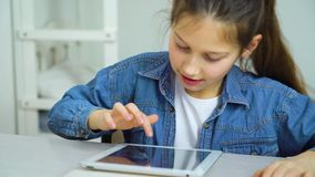 Happy little girl touching screen of tablet while playing games online stock video