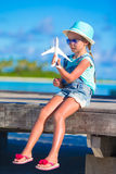 Happy little girl with toy airplane in hands on Stock Photos