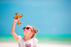 Happy little girl with toy airplane in hands on white sandy beach Royalty Free Stock Images