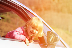 Happy little girl travel by car in autumn nature Royalty Free Stock Photos