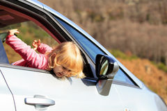 Happy little girl travel by car in nature Royalty Free Stock Photo