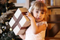 Happy little girl try to open christmas gift box stock photo