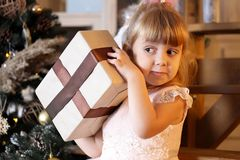 Happy little girl try to open christmas gift box stock image