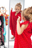 Happy little girl trying on dresses Stock Photos