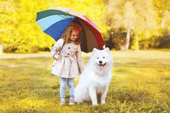 Happy little girl with umbrella walking with dog in the park Stock Images