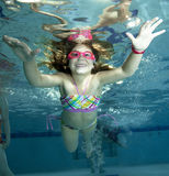 Happy little girl underwater in pool Royalty Free Stock Images