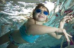Happy little girl underwater in pool Royalty Free Stock Photo