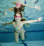 Happy little girl underwater in pool Royalty Free Stock Photos