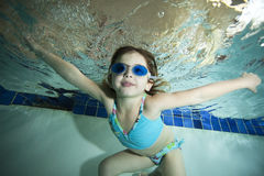 Happy little girl underwater in pool Stock Images