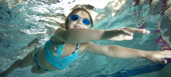 Happy little girl underwater in pool Stock Photo
