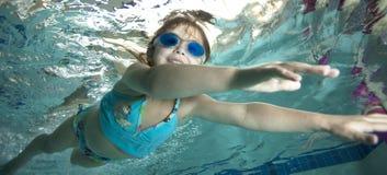 Happy little girl underwater in pool stock photo