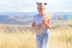 Blonde little girl holding spikes of wheat and ears of oats in golden harvest field. royalty free stock images