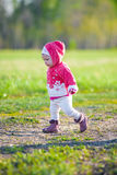 Happy little girl walking in the meadow and Royalty Free Stock Photos