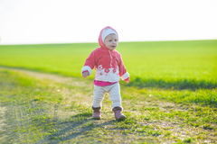 Happy little girl walking in the meadow and Royalty Free Stock Photography