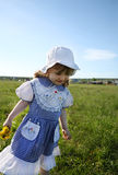Happy little girl walks on green field Stock Photos