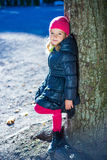 Happy little girl in warm clothes posing in park Stock Image