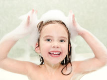 Happy little girl washing in bath with foam Royalty Free Stock Photos