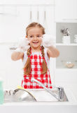 Happy little girl washing the dishes Stock Photos
