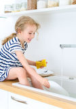Happy little girl washing the dishes. Stock Images