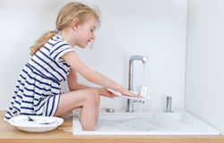 Happy little girl washing the dishes. Royalty Free Stock Image