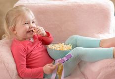 Happy little girl watching TV at home. Happy little girl with blonde hair sitting on a pink plush chair eating popcorn and watching a movie on TV Stock Images