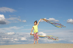 Happy little girl waving with colorful ribbons Stock Image
