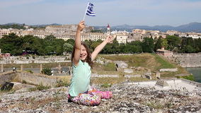 Happy little girl waving with Greek flag Corfu town stock video footage