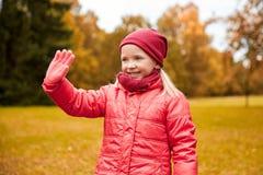 Happy little girl waving hand in autumn park stock photo