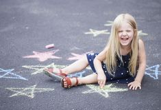 Happy little girl sitting on asphalt and laughing royalty free stock photo