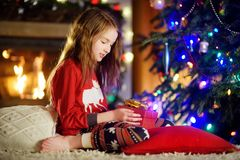 Happy little girl wearing Christmas pajamas playing by a fireplace in a cozy dark living room on Christmas eve Stock Image