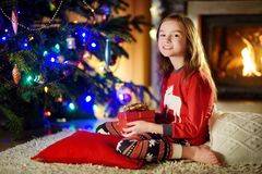 Happy little girl wearing Christmas pajamas playing by a fireplace in a cozy dark living room on Christmas eve Stock Photos