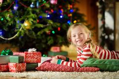 Happy little girl wearing Christmas pajamas playing by a fireplace in a cozy dark living room on Christmas eve. Royalty Free Stock Photos