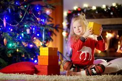 Happy little girl wearing Christmas pajamas playing by a fireplace in a cozy dark living room on Christmas eve Royalty Free Stock Photos
