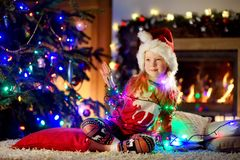 Happy little girl wearing Christmas pyjamas playing by a fireplace in a cozy dark living room on Christmas eve Royalty Free Stock Image