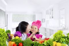 Little girl with vegetables kissed by mom Stock Photography