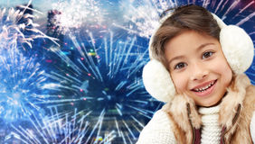 Happy little girl wearing earmuffs over firework Royalty Free Stock Images