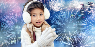 Happy little girl wearing earmuffs over firework Royalty Free Stock Photos