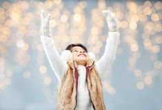 Happy little girl wearing earmuffs over lights Royalty Free Stock Photo
