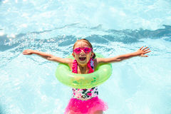 Happy little girl wearing flotation ring in pool. Portrait of happy little girl wearing swimsuit and goggles learning to swim in pool in flotation ring and stock image