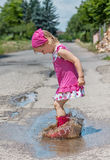 Happy little girl wearing pink rain boots jumping into a puddle. Stock Photography