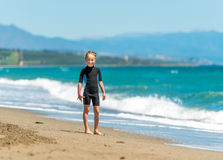 Happy little girl in a wetsuit. On the coast Royalty Free Stock Photo