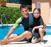 Happy little girl in a wetsuit. Cute little girl with her father in a wetsuit near the pool Stock Photos