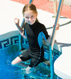 502eef026f Happy little girl in a wetsuit. Cute little girl in a wetsuit near the pool