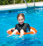 690ffabe45 Happy little girl in a wetsuit. Cute little girl swims in a wetsuit with a